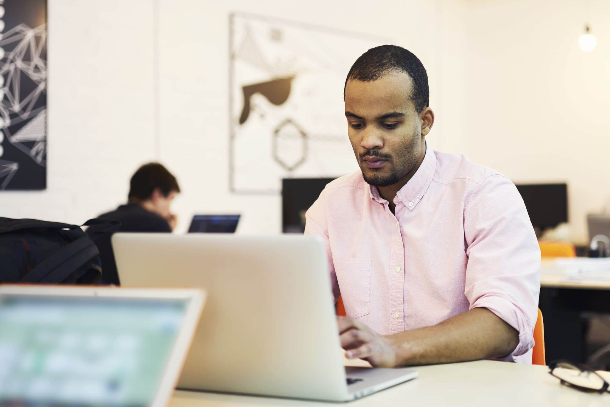 Man in office typing on laptop